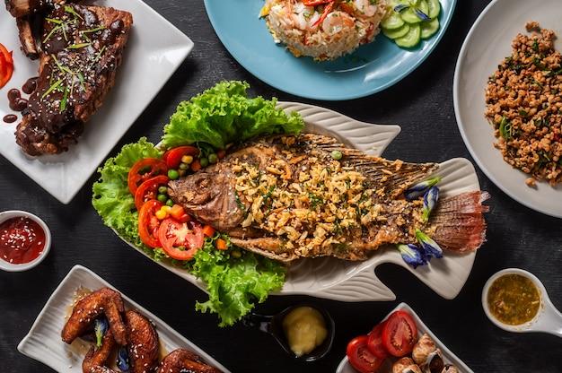 Vue de dessus du groupe de nourriture sur bois, poisson frit au milieu, vue de dessus.