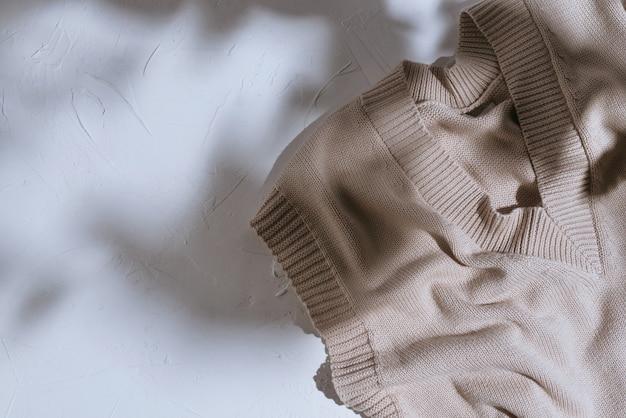 Vue de dessus du haut sans manches beige en coton tricoté sur fond de ciment blanc avec des ombres sombres