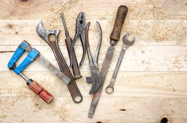 Vue de dessus du jeu d'outils vieux et rouillé sur établi en bois de pin naturel. concept de travail et de bricolage.