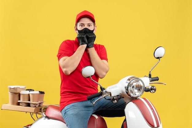 Vue de dessus du jeune adulte effrayé portant un chemisier rouge et des gants de chapeau en masque médical délivrant l'ordre assis sur un scooter sur fond jaune