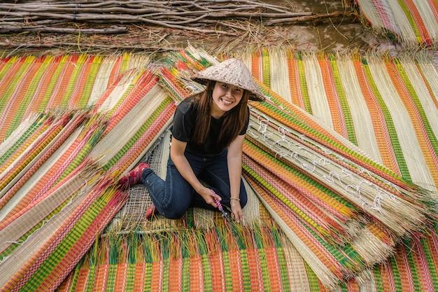 Vue de dessus du jeune artisan vietnamien fabriquant avec bonheur les tapis vietnamiens traditionnels