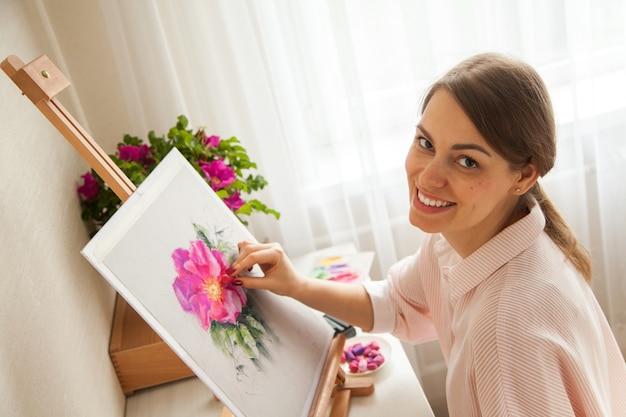 Vue de dessus du jeune artiste caucasien jolie fille peint croquis de fleur rose assis à table avec bouquet de rose et de pivoines avec des fournitures de peinture et des pastels secs. concept de créativité et de passe-temps