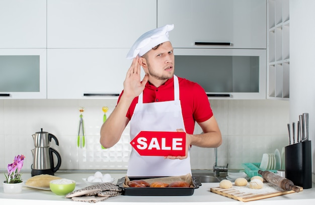 Vue de dessus du jeune chef masculin montrant un signe de vente et écoutant les commérages dans la cuisine blanche