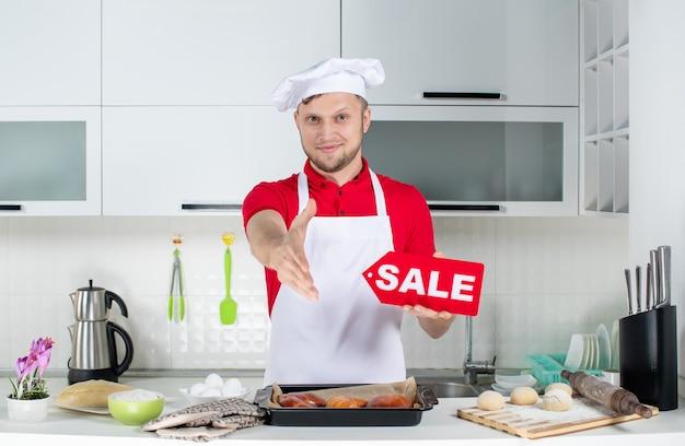Vue de dessus du jeune chef masculin souriant tenant une pancarte de vente et accueillant quelqu'un dans la cuisine blanche