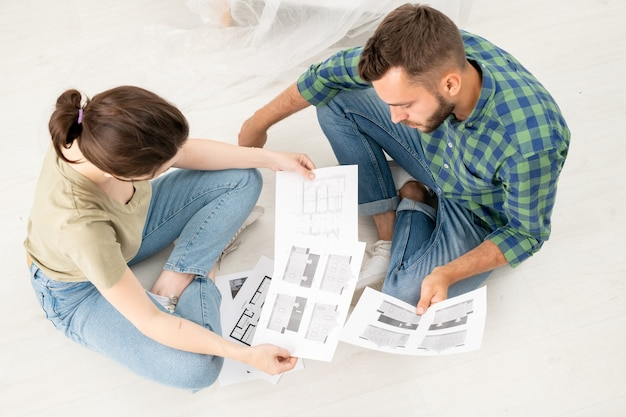 Vue de dessus du jeune couple concentré assis avec les jambes croisées sur le sol et l'analyse des plans de maison tout en pensant à la rénovation
