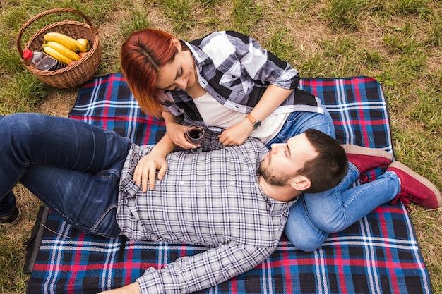 Vue de dessus du jeune couple profitant du pique-nique