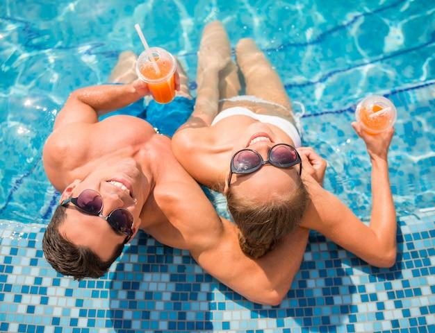 Vue de dessus du jeune couple se détendre dans la piscine de la station.