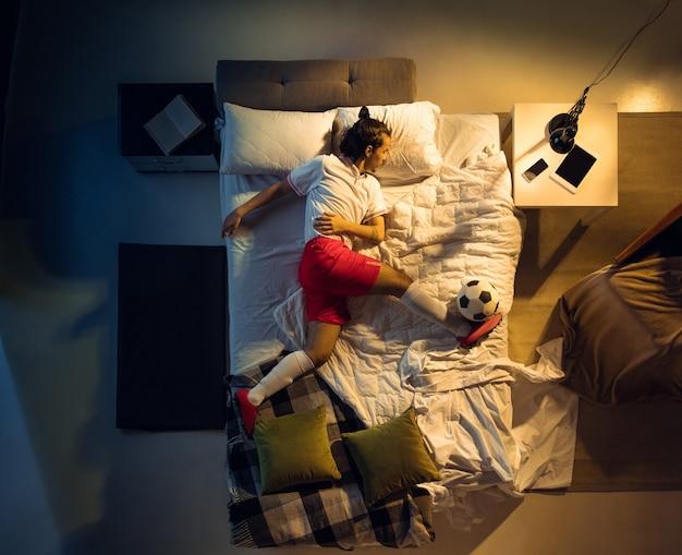 Vue de dessus du jeune footballeur de football professionnel dormant dans sa chambre en vêtements de sport avec ballon
