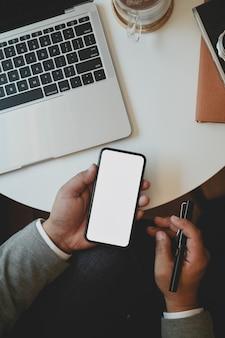 Vue de dessus du jeune homme d'affaires tenant un smartphone à écran blanc tout en travaillant sur son projet