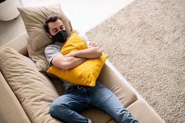 Vue de dessus du jeune homme au masque facial embrassant un oreiller et dormant sur un canapé pendant l'isolement du coronavirus