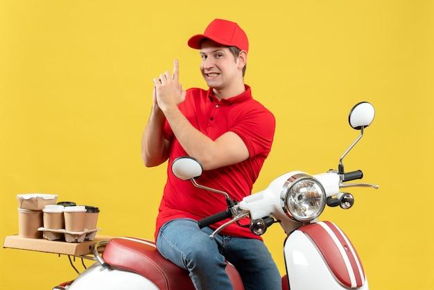 Vue de dessus du jeune homme confiant portant chemisier rouge et chapeau délivrant des commandes faisant le geste des armes à feu sur fond jaune