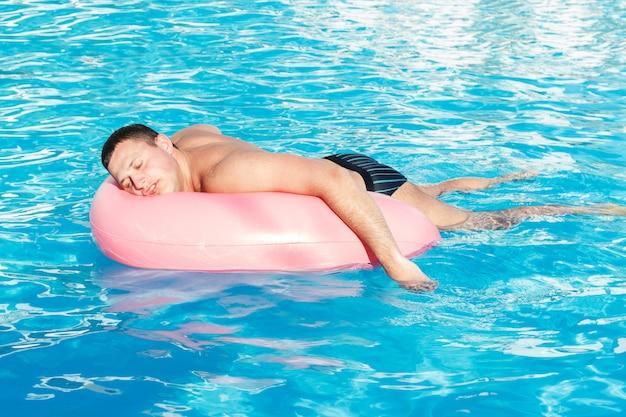 Vue de dessus du jeune homme ivre nage avec cercle rose dans la piscine.