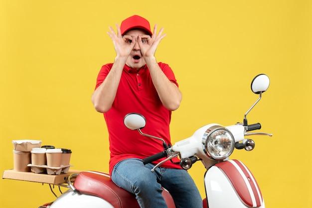 Vue de dessus du jeune homme portant un chemisier rouge et un chapeau livrant des commandes faisant des gestes de lunettes sur fond jaune