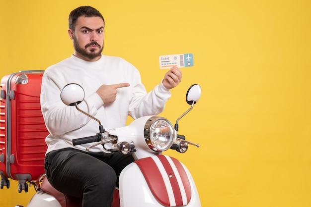 Vue de dessus du jeune homme voyageur émotionnel incertain assis sur une moto avec une valise dessus tenant un billet sur jaune