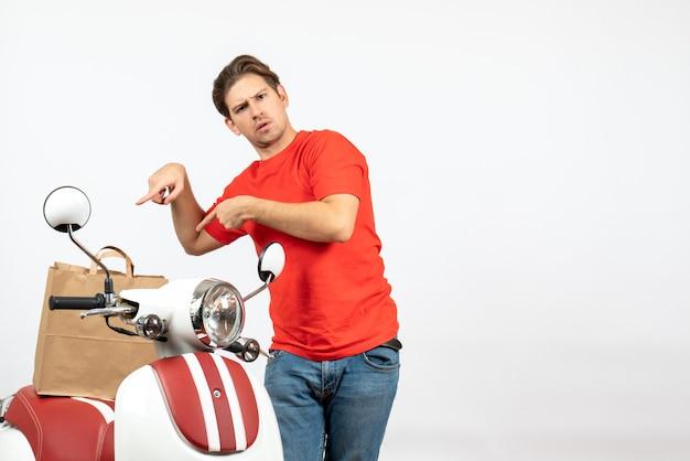Vue de dessus du jeune livreur choqué en uniforme rouge debout près de scooter montrant un document sur un mur blanc