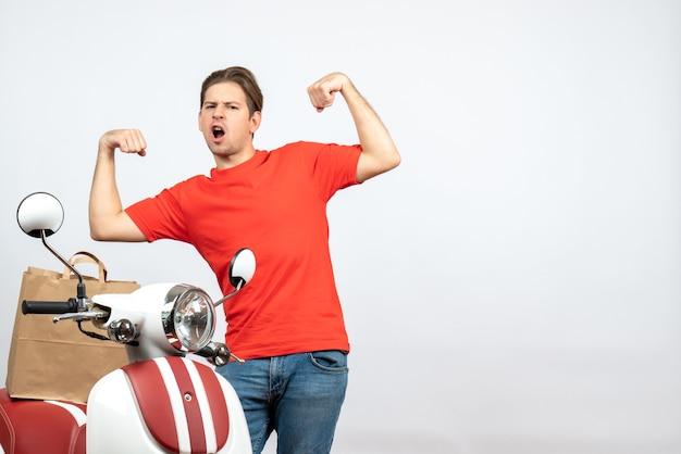 Vue de dessus du jeune livreur fier en uniforme rouge debout près de scooter sur mur blanc
