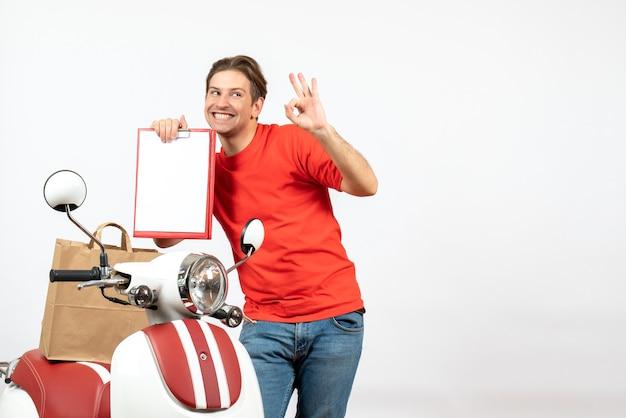 Vue de dessus du jeune livreur souriant en uniforme rouge debout près de scooter montrant un document faisant des gestes de lunettes sur un mur blanc