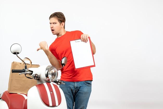 Vue de dessus du jeune livreur surpris en uniforme rouge debout près de scooter montrant le document pointant vers l'arrière sur le mur blanc