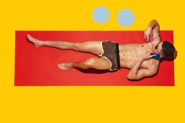 Vue de dessus du jeune modèle masculin caucasien reposant sur la station balnéaire