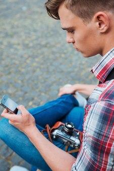 Vue de dessus du jeune photographe avec un appareil photo à l'ancienne tapant quelque chose sur son téléphone portable alors qu'il était assis à l'extérieur