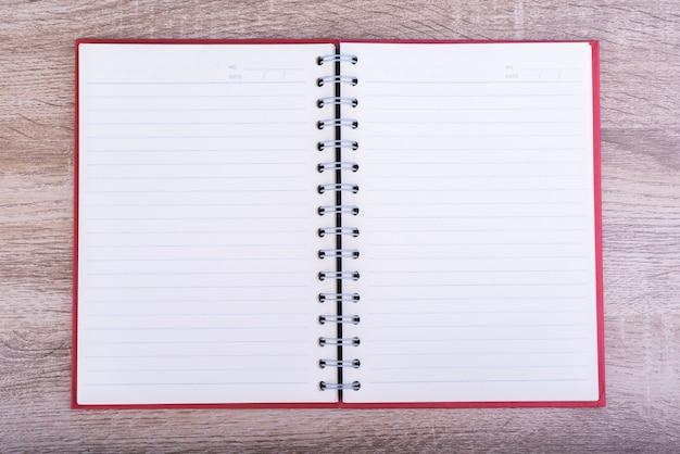 Vue de dessus du journal ouvert ou du carnet de notes mis sur une table en bois.
