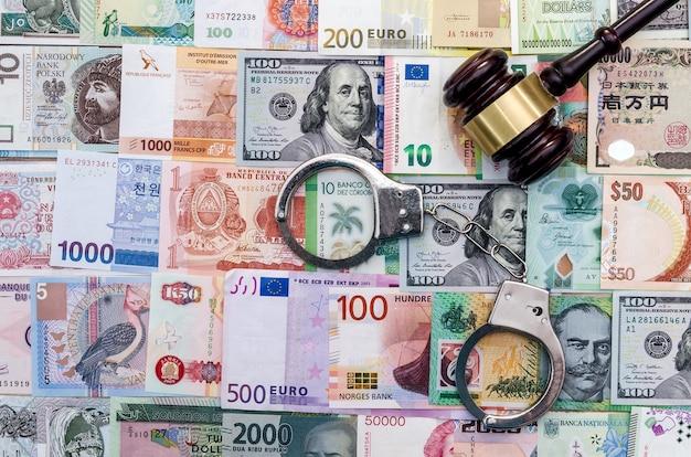 Vue de dessus du juge marteau et des menottes sur la collection mondiale de l'argent