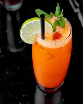 Vue de dessus du jus de carotte avec une tranche de citron vert et min
