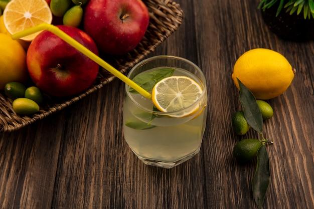 Vue de dessus du jus de citron frais avec des pommes, des citrons et des kinkans sur un plateau en osier sur un mur en bois