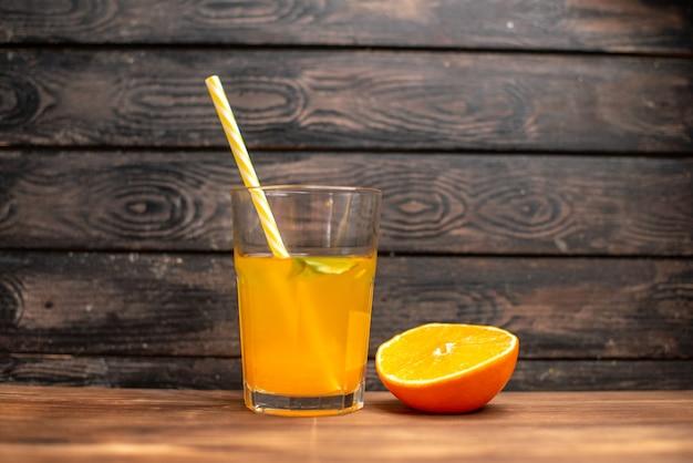 Vue de dessus du jus d'orange frais dans un verre servi avec de la menthe en tube et du citron vert sur une table en bois