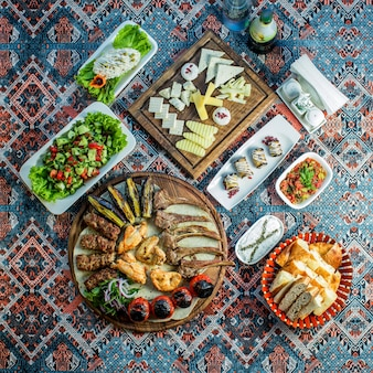 Vue de dessus du kebab mixte servi avec une assiette de fromage de salade de légumes frais et des rouleaux d'aubergine sur un tapis coloré