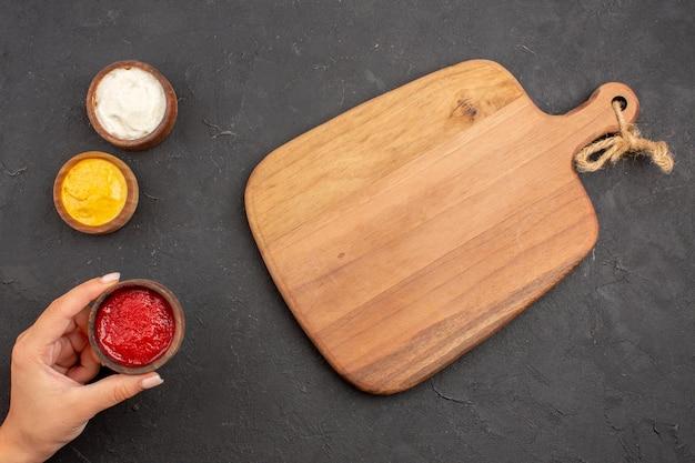 Vue de dessus du ketchup et de la moutarde avec de la mayyonaise à l'intérieur de petits pots sur fond noir