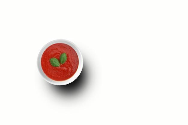 Vue de dessus du ketchup de tomates sur un bol blanc avec deux feuilles. vue de dessus du ketchup de tomates sur un bol blanc. adapté à votre élément de conception.
