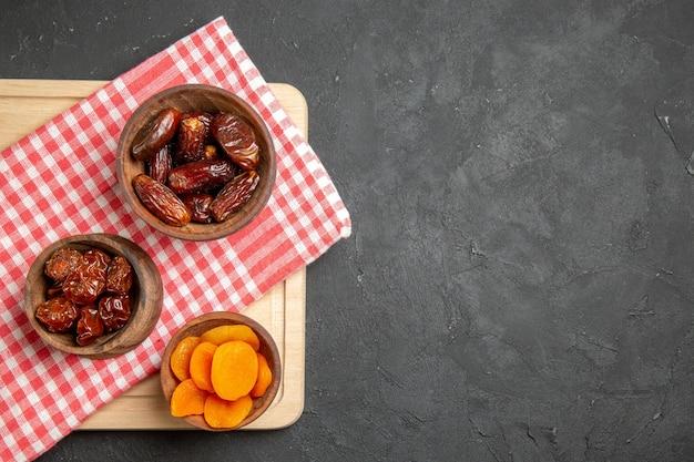 Vue de dessus du khurma sec aux abricots secs sur une surface sombre aux raisins secs