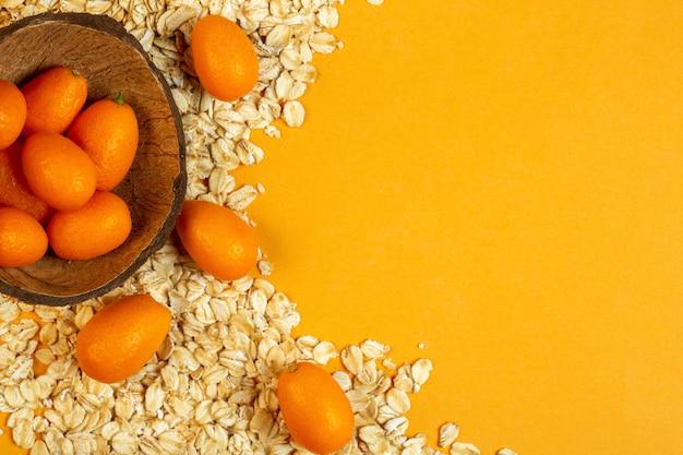 Vue de dessus du kumquat dans un bol en bois et des flocons d'avoine avec copie espace sur jaune