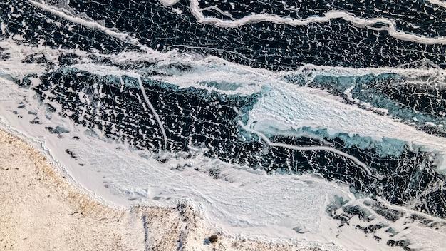 Vue de dessus du lac baïkal gelé. glace, fissures, neige, rivage, arbres. région d'irkoutsk, russie