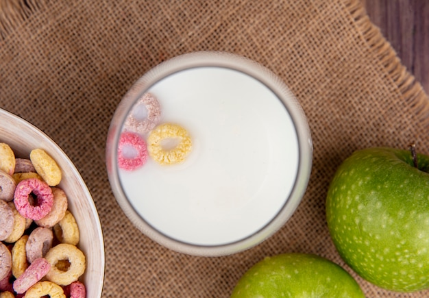 Vue de dessus du lait sur un bol avec des céréales colorées sur un bol sur une toile de sac sur une surface en bois