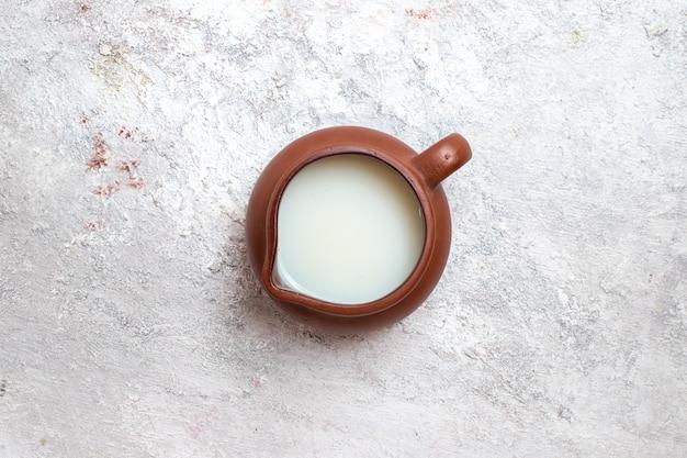Vue de dessus du lait frais à l'intérieur de la cruche brune sur la surface blanche lait produit laitier crème au fromage