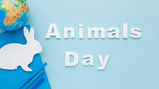 Vue de dessus du lapin en papier avec la planète terre pour la journée des animaux