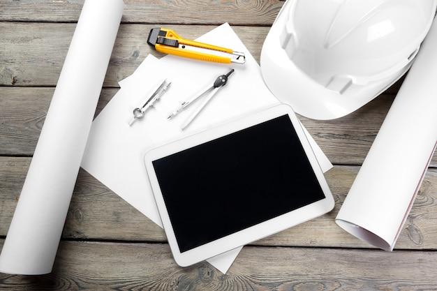 Vue de dessus du lieu de travail d'architecte avec papier blueprint et tablette numérique avec écran blanc