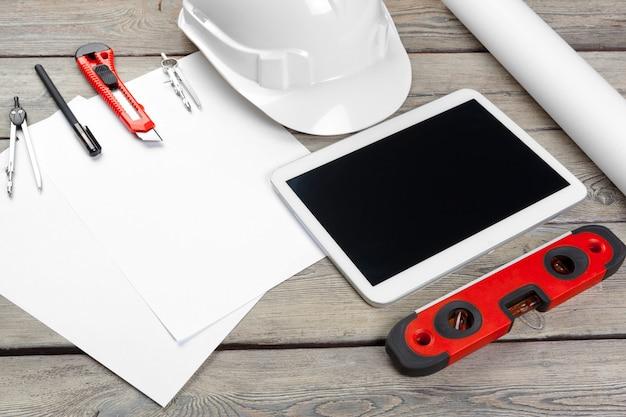 Vue de dessus du lieu de travail de l'architecte avec papier blueprint et tablette numérique