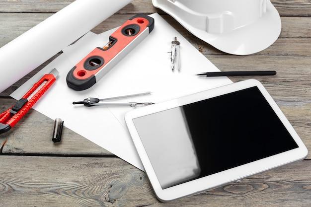 Vue de dessus du lieu de travail de l'architecte avec papier et tablette numérique avec écran blanc