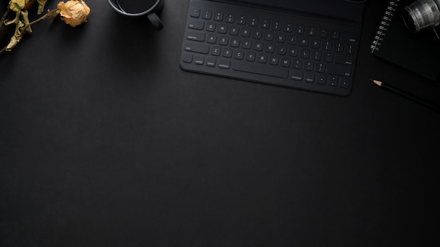 Vue de dessus du lieu de travail avec clavier sans fil, espace copie, appareil photo et roses sèches sur tableau noir