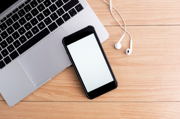Vue de dessus du lieu de travail de concepteur avec maquette de smartphone sur table.