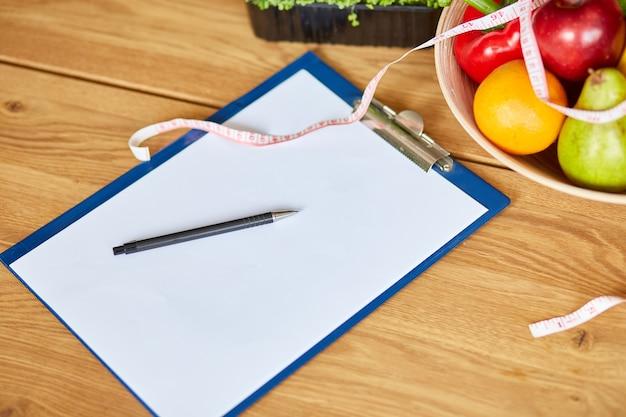 Vue de dessus du lieu de travail d'un diététicien nutritionniste avec un blanc pour un stylo de régime alimentaire ruban à mesurer et bol avec des légumes et des fruits sains