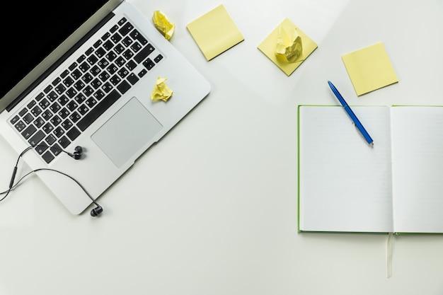 Vue de dessus du lieu de travail minimaliste à domicile avec ordinateur portable et bloc-notes