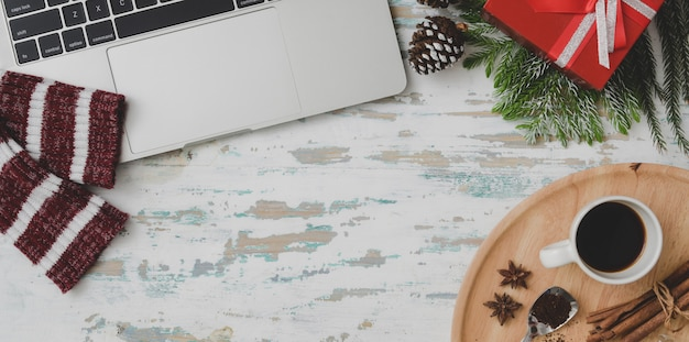 Vue de dessus du lieu de travail de noël décoré avec ordinateur portable, tasse à café et présente sur un bureau en bois vintage