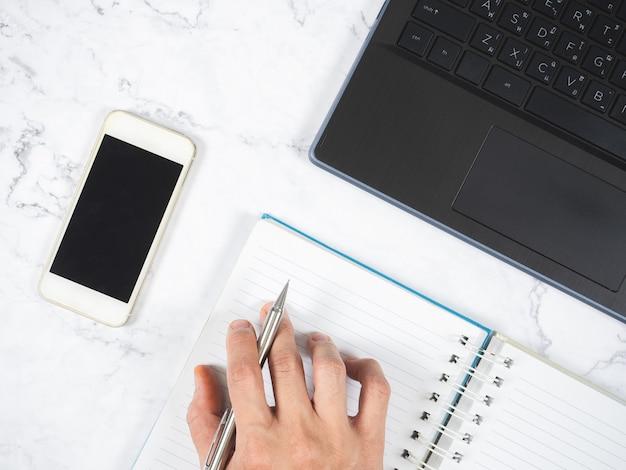 Vue de dessus du lieu de travail avec stylo sur ordinateur portable smartphome et ordinateur portable sur la table travail à domicile