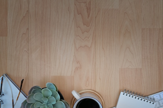 Vue de dessus du lieu de travail avec une tasse de café, clavier, fournitures de bureau sur une table en bois