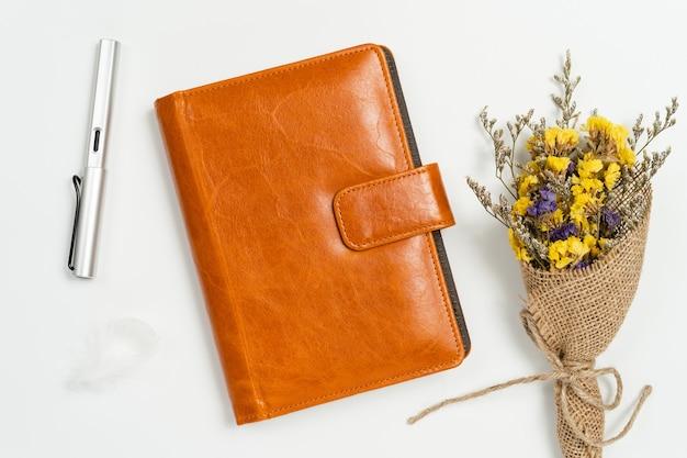 Vue de dessus du livre de journal en cuir marron avec stylo et fleurs statiques sur fond blanc