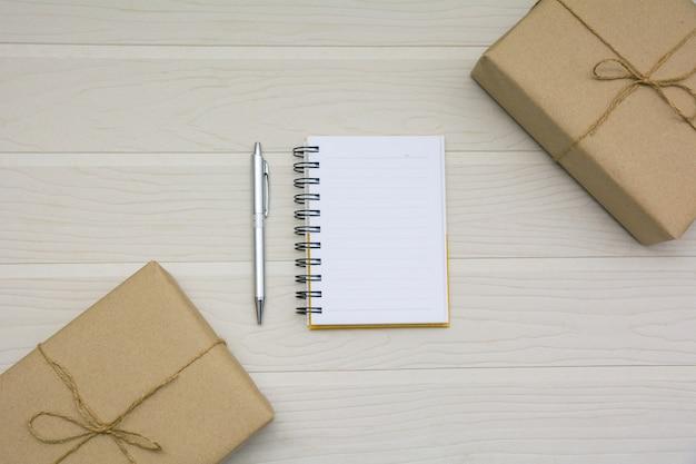 Vue de dessus du livre ouvert. livre ouvert avec un stylo et des boîtes sur fond en bois et copie espace